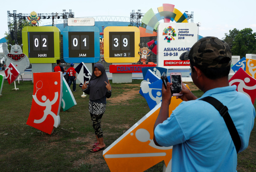 A woman poses with a clock counting down to the opening of the Asian Games at Jakabaring Sports City on Thursday. (Reuters Photo/Edgar Su)