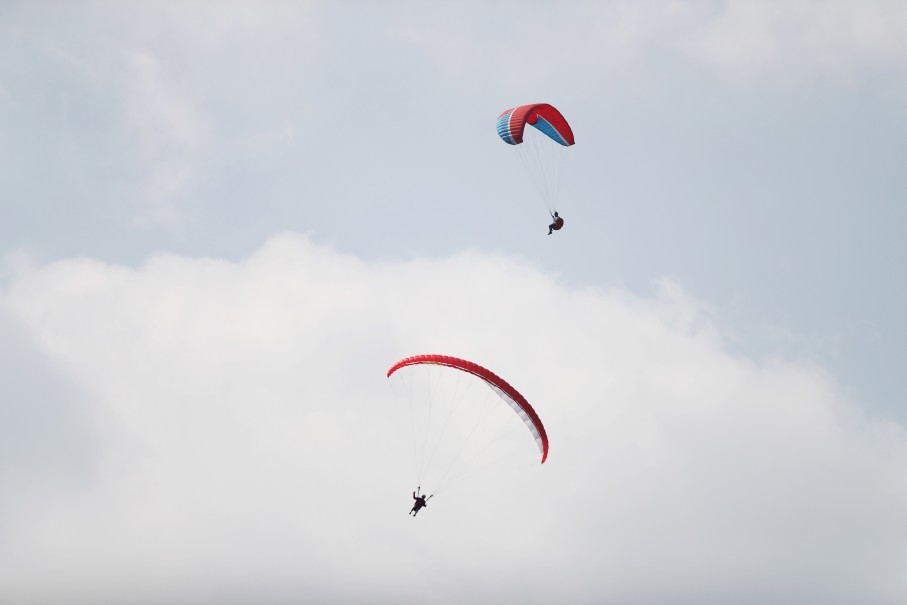 Bimal Adhikari of Nepal and Aris Apriansyah of Indonesia compete in paragliding at Gunung Mas Puncak, West Java, on Monday (20/08). The Asian Games' outdoor sports like paragliding depend on accurate weather forecasts. (Reuters Photo/Dyjan Tjhia)