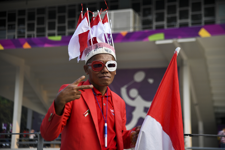 Haryanto, 54, a devout supporter of Indonesia's badminton team, watches the 2018 Asian Games badminton event. (JG Photo/Yudha Baskoro)