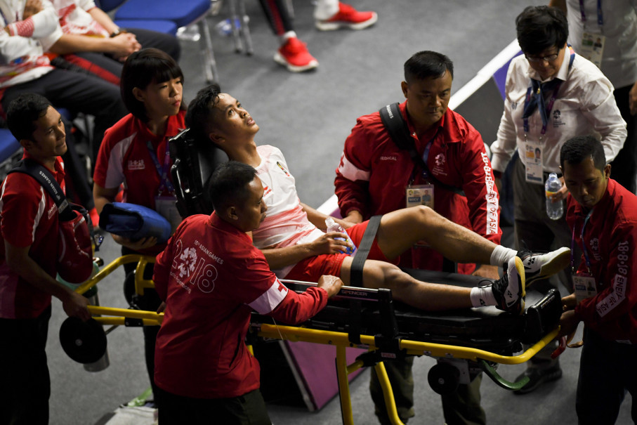 Indonesian men's singles player Anthony Ginting is carried off on a stretcher after injury forced him to abandon his match against  Shi Yuqi of China on Wednesday. (JG Photo/Yudha Baskoro)