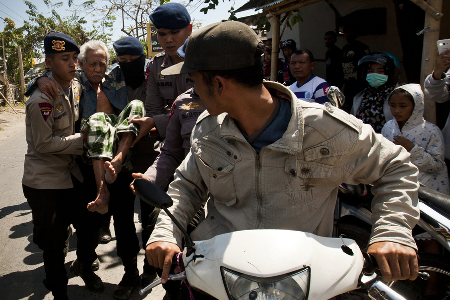 Police officers evacuating an elderly man on Tuesday, two days after the deadly earthquake. (JG Photo/Yudha Baskoro)