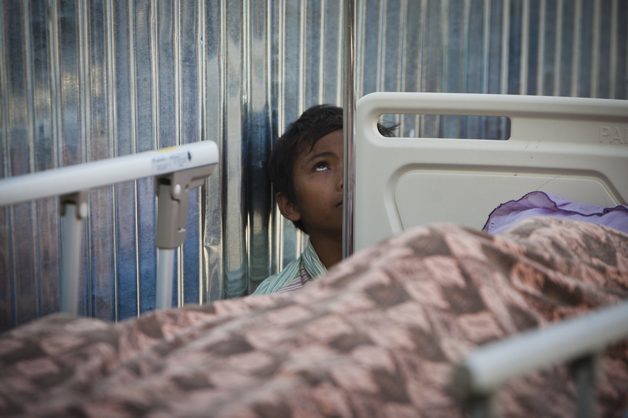A child sits next to his mother's body in Tanjung Public Hospital in North Lombok on Tuesday. (JG Photo/Yudha Baskoro)