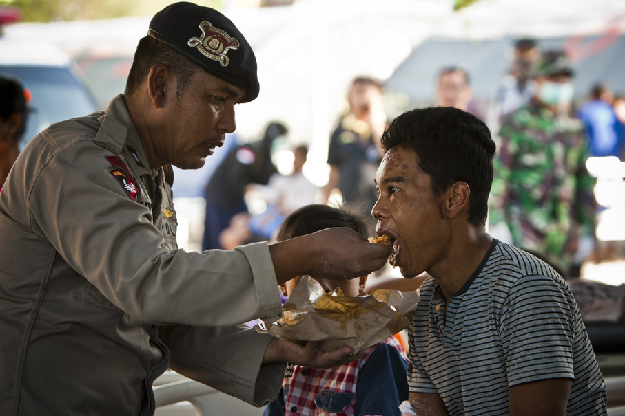 A police officer feeds an earthquake victim in North Lombok. (JG Photo/Yudha Baskoro)