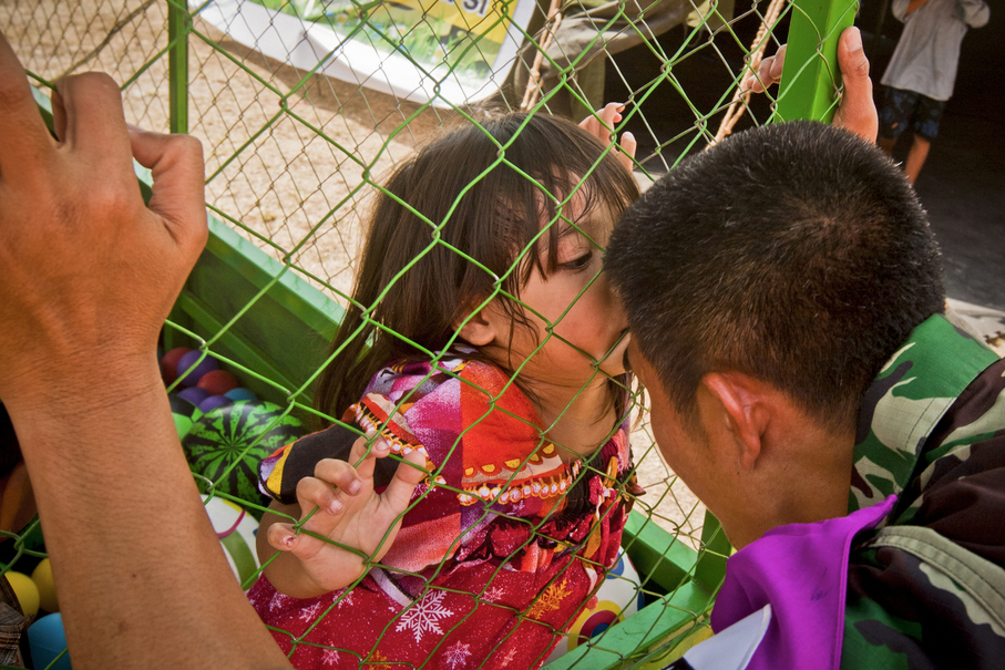 A child kisses a soldier during a play therapy session at a temporary shelter in Tanjung, North Lombok district, on Friday. (JG Photo/Yudha Baskoro)