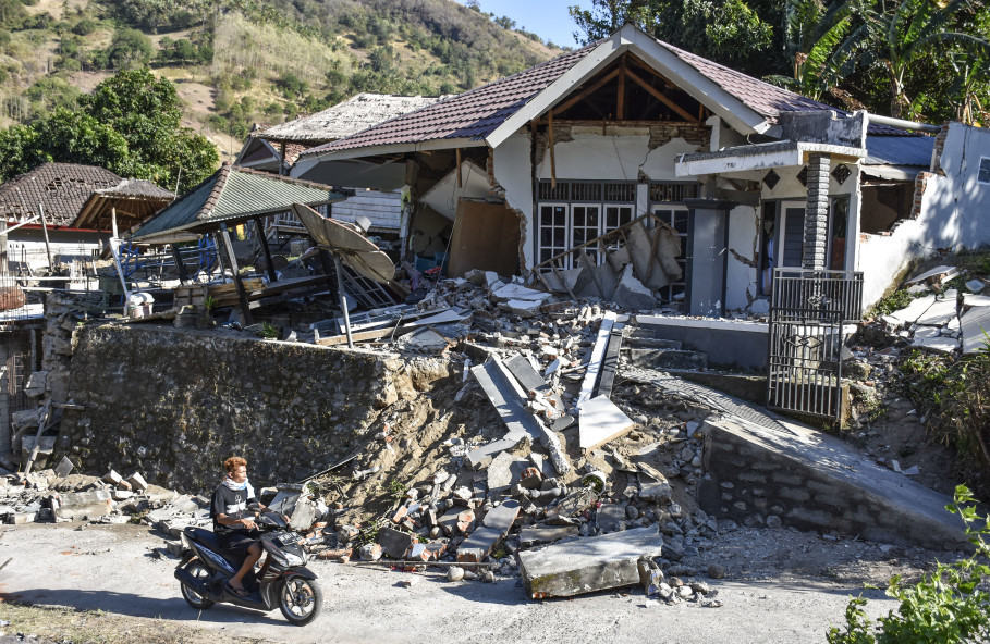 A motorcyclist passes a house destroyed by the Lombok earthquake in Pemenang, Tanjung, North Lombok, on Monday (06/08). (Antara Photo/Ahmad Subaidi)
