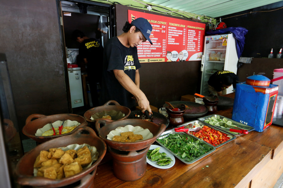 A cook prepares food at a restaurant which offers free meals for people who can show they have recently changed U.S. dollars for Indonesian rupiah at their outlet in Jakarta on Sept. 7, 2018. (Reuters Photo/Willy Kurniawan)