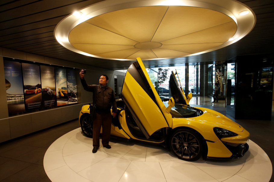 A man takes a selfie inside a McLaren showroom located in a shopping mall in Jakarta, Indonesia, Sept. 7, 2018. (Reuters Photo/Willy Kurniawan)