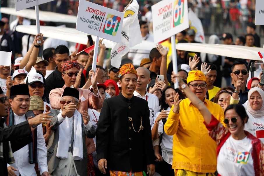 Jokowi and his running mate, Ma'ruf Amin, left, walk in a parade during the ceremony marking the start of the campaigning period for the 2019 presidential election. (Reuters Photo/Darren Whiteside)