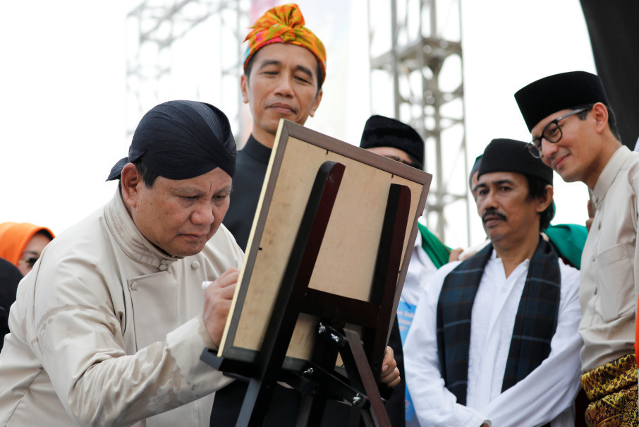 President Jokowi looks on while Prabowo signs a pledge to conduct a peaceful election campaign. (Reuters Photo/Darren Whiteside)