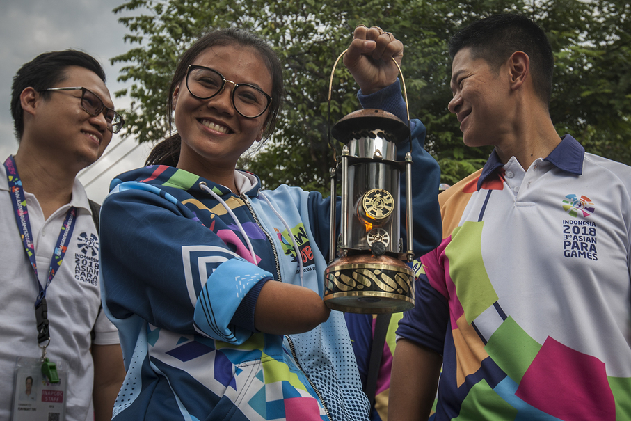 Athlete Nanda Mei Solikhah, center, carries the lantern, accompanied by Indonesia Asian Para Games Organizing Committee (Inapgoc) chairman Raja Sapto Oktohari, right, during the parade in Solo. (JG Photo/Yudha Baskoro)