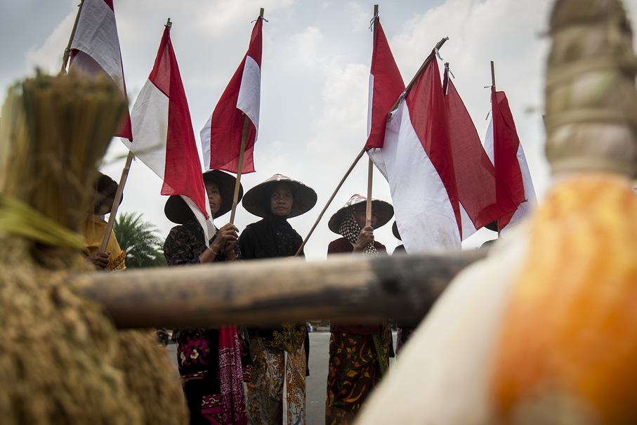 Farmers carrying Indonesian national flags and sheaves of rice during the protest. (JG Photo/Yudha Baskoro)