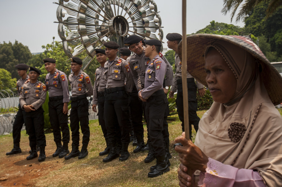 Police officers keep an eye on the group while they protest front of the State Palace. (JG Photo/Yudha Baskoro)
