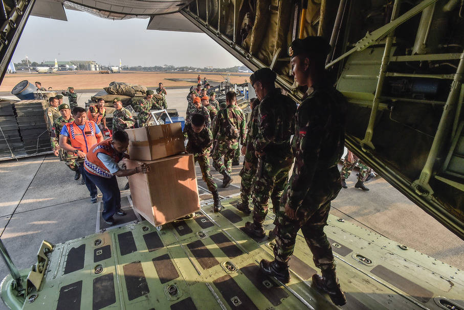 Military personnel loading equipment and emergency supplies into a cargo plane at Halim Perdanakusuma Air Force Base in East Jakarta on Saturday morning, to be dispatched to in Palu and Donggala. (Antara Photo/Muhammad Adimaja)