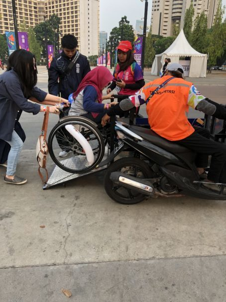 A motorcycle taxi loading a passenger at the 2018 Asian Para Games. (JG Photo/Diella Yasmine)
