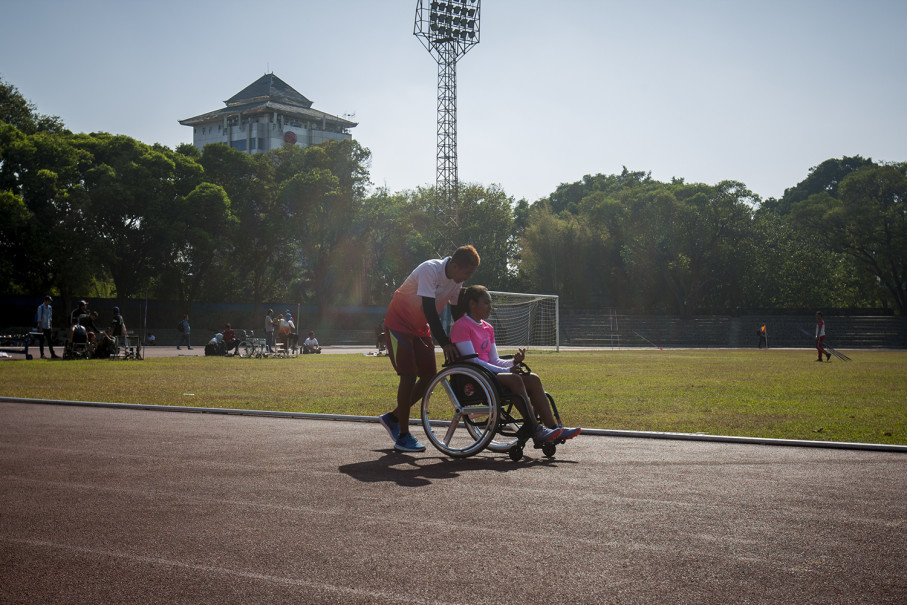 An athlete helps a teammate on the track. (JG Photo/Yudha Baskoro)