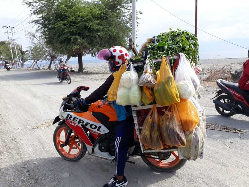 A merchant on motorcycle selling vegetables and cooking oil. (JG Photo/Telly Nathalia)