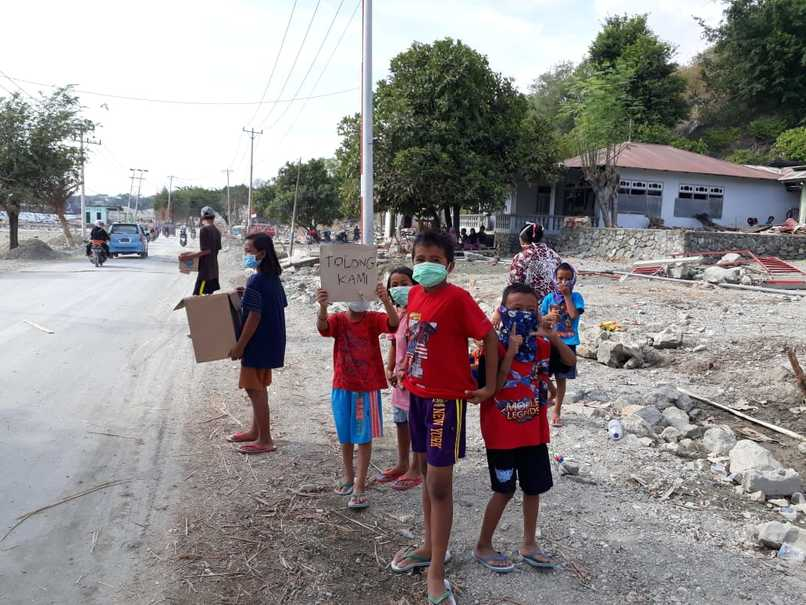 Children asking for donations from passersby in Loly village. At least three villagers are still missing. (JG Photo/Telly Nathalia)