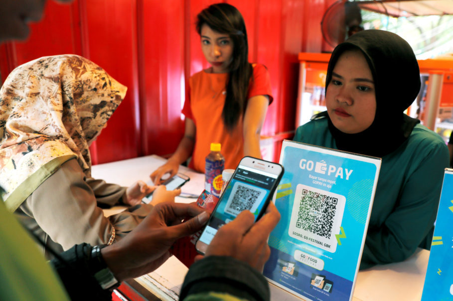A customer uses a smartphone to scan a QR code to pay for food using Go-Pay during a festival in Jakarta last month. (Reuters Photo/Beawiharta)