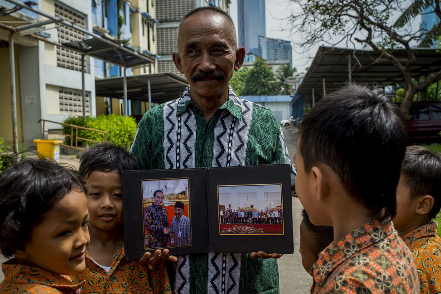 Kinong, who is also known as Pak Kumis (Mr Moustache), shows photos of him meeting President Joko 'Jokowi' Widodo on National Education day last year.