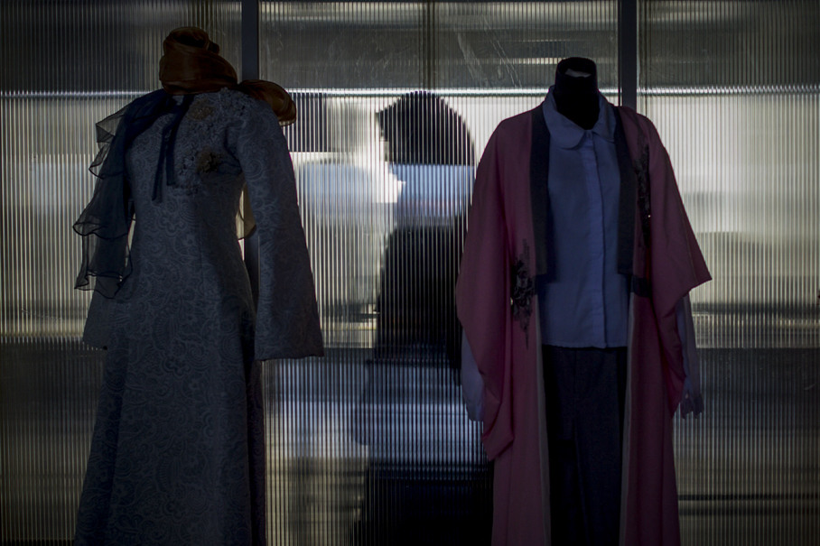 The silhouette of a woman is seen behind two pieces that were featured in the fashion show, which took place in Click Square, Bandung. (JG Photo/Yudha Baskoro)