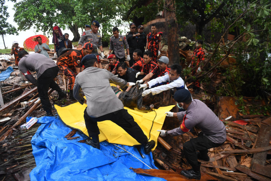 Police officers and volunteers a victim from a building in Banten that was destroyed by the Sunda Strait tsunami. (Antara Photo/Akbar Nugroho Gumay)