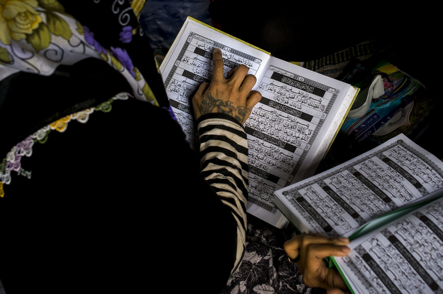 A tattooed woman recites the Koran during class. Tattoos and piercings are considered haram in Islam because it involves self-harm. (JG Photo/Yudha Baskoro)