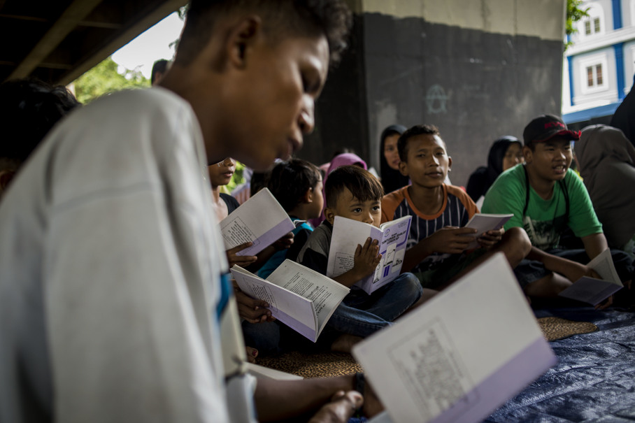 People of various ages gather to study a guidebook on how to pray correctly. The books are handed out to everyone attending the classes. (JG Photo/Yudha Baskoro)