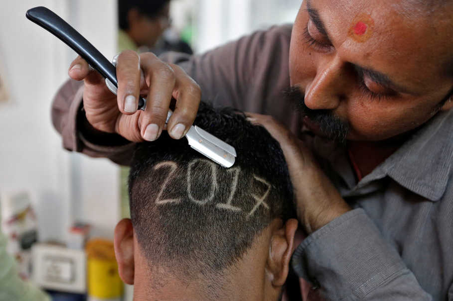 A barber razor cuts '2017' on the back of his customer's head to welcome the new year in Ahmedabad, India, on Dec. 31, 2016. (Reuters Photo/Amit Dave)