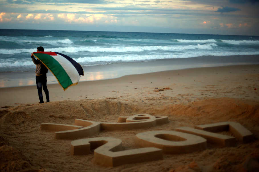 Palestinian artist Yazed Abu Jarad holds a Palestinian flag after making a sand sculpture that reads 'Welcome 2017' at a beach in the northern Gaza Strip on Dec. 31, 2016. (Reuters Photo/Suhaib Salem)