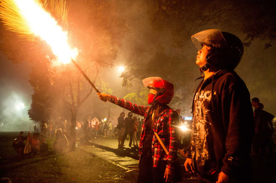 A woman holds out a sparkler at the Bajra Sandhi Monument during New Year celebrations in Denpasar, Bali, on Jan. 1, 2017. (Reuters Photo/Agung Parameswara)