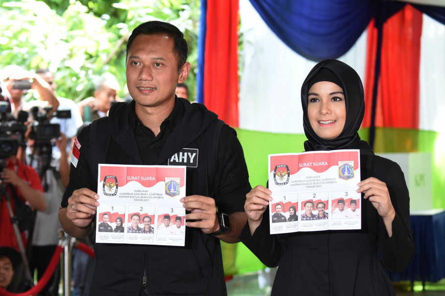 Jakarta governor candidate Agus Harimurti Yudhoyono, the son for former president Susilo Bambang Yudhoyono, and his wife Annisa Pohan register their vote at a polling station in Rawa Barat, South Jakarta, on Wednesday (15/02). (Antara Photo/Akbar Nugroho Gumay)