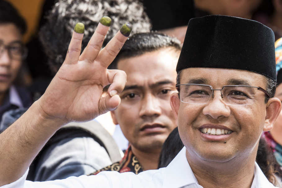Jakarta governor candidate Anies Baswedan, a former education minister, greets the crowd with his customary three-fingered salute after registering his vote at a polling station in West Cilandak, South Jakarta, on Wednesday (15/02). (Antara Photo/Agung Rajasa)