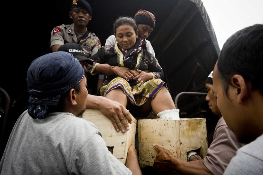 A Kendeng farmer, feet still cast in cement, is lifted into a police truck. (JG Photo/Yudha Baskoro)