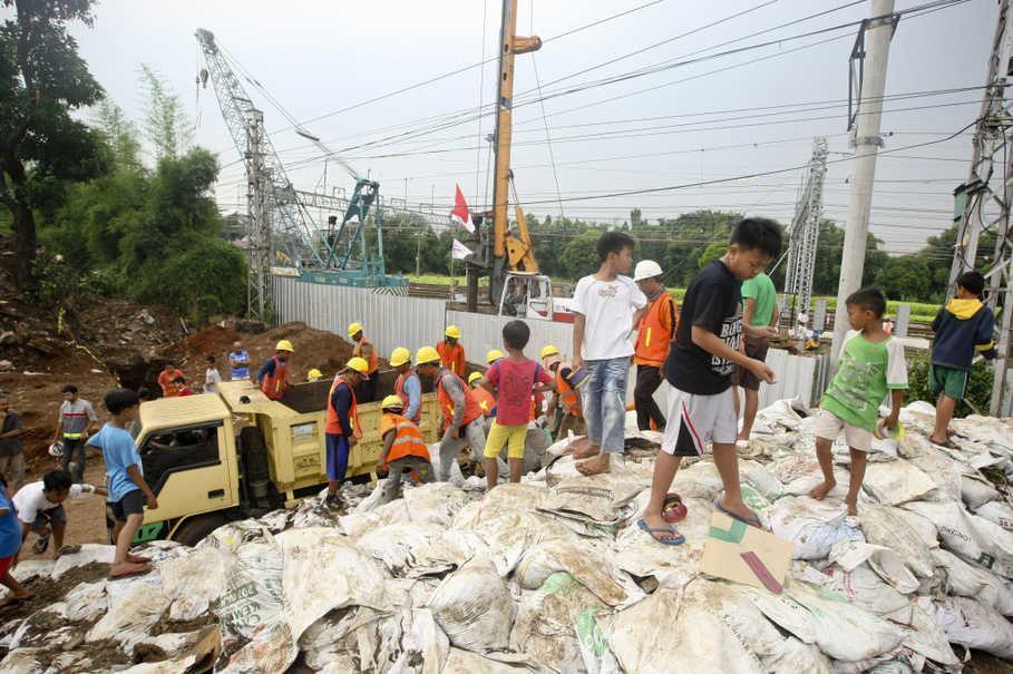 Children play on sandbags stacked up outside the construction site. (JG Photo/Yudha Baskoro)
