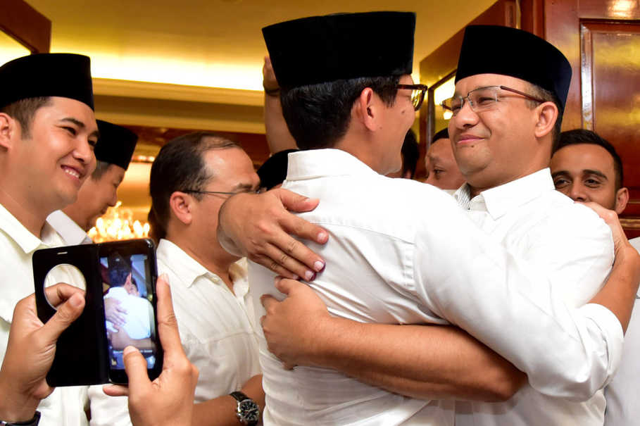 Anies Baswedan, right, and his running mate Sandiaga Uno, embrace after quick count results have shown them with a lead in the second round of Jakarta's gubernatorial election on Wednesday (19/04). (Antara Photo/Dedi Wijaya)