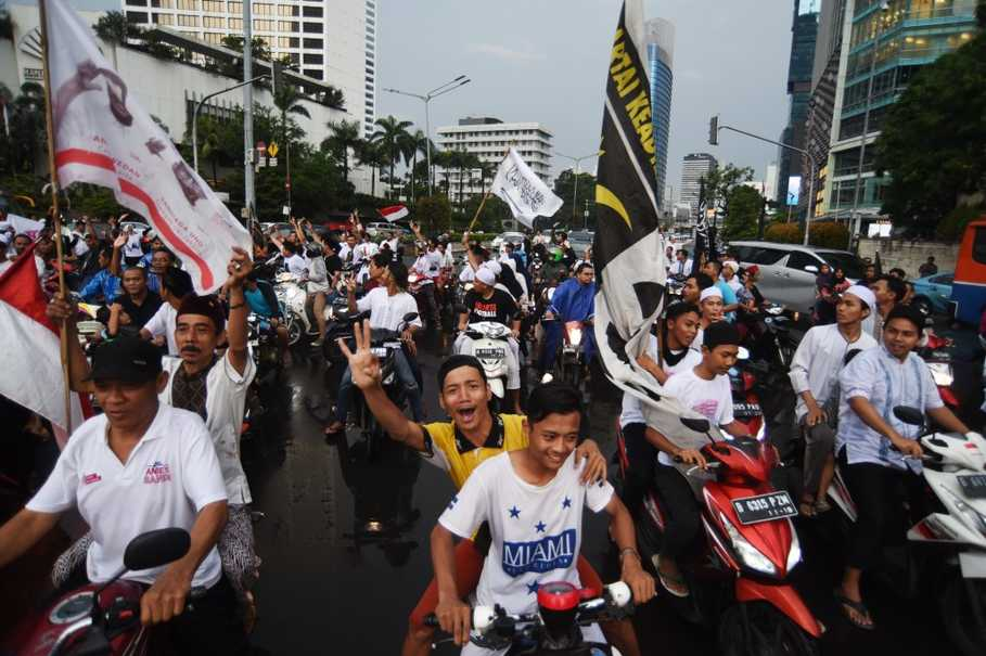 Supporters of gubernatorial candidate Anies Baswedan and his deputy Sandiaga Uno celebrate their win at the Hotel Indonesia roundabout in Jakarta. (Antara Photo/Akbar Nugroho Gumay)
