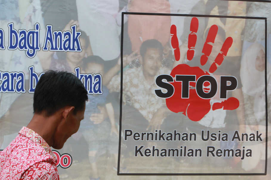 A resident walks past a 'Stop violence against children' poster in Rembang, Central Java, on April 19, 2017. (JG Photo/Yudhi Sukma Wijaya)