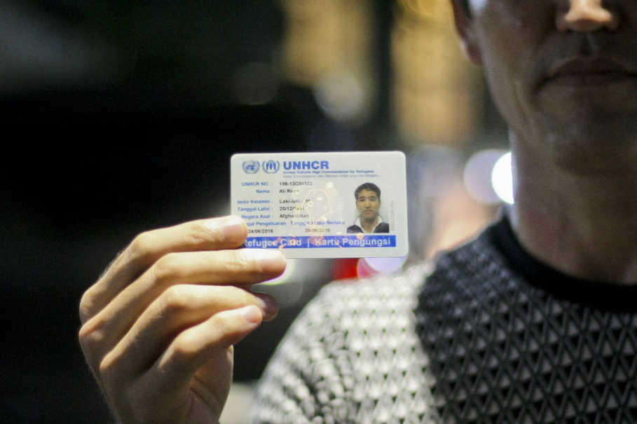 Ali Reza from Afghanistan holds up his UNHCR refugee card. (JG Photo/Yudha Baskoro)