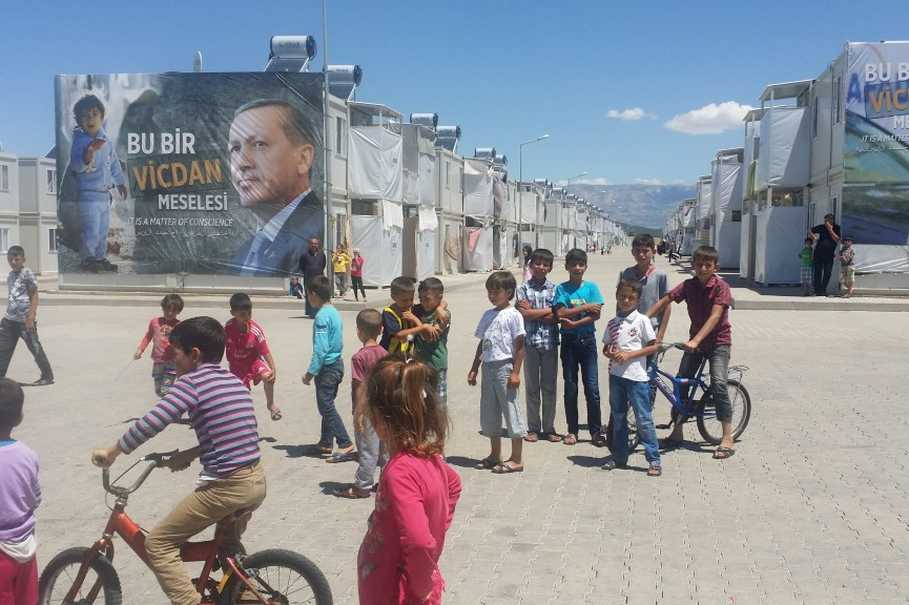 Refugee children at the Kahramanmaraş camp play in front of a banner with a picture of Turkish President Recep Tayyip Erdoğan and the words 'It is a matter of conscience.' (Photo courtesy of Javier Delgado Rivera)