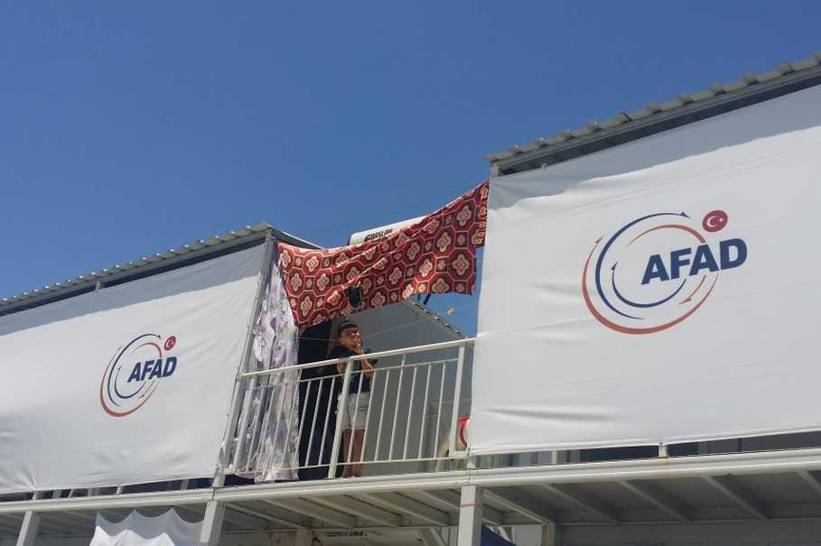 A child leans on the balcony in between two containers at the Osmaniye camp. The logo of Tukey's Disaster and Emergency Management Agency (AFAD) is printed on the canvas, which screens off the entrance of the living units. (Photo courtesy of Javier Delgado Rivera)