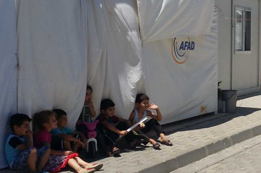 Several children at the Kahramanmaraş camp smile and wave under the thin shade projected by a container block. (Photo courtesy of Javier Delgado Rivera)