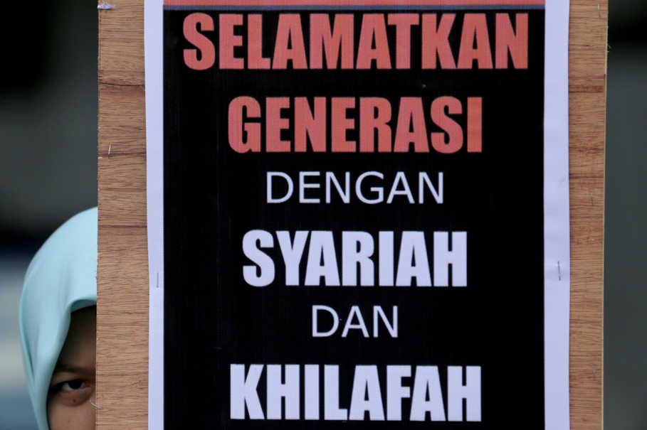 "A Hizbut Tahrir poster reads: ""Save the generation with Syariah and Khilafah."" (Antara Photo/Nova Wayudi)"