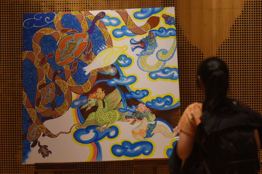 A visitor looks at a collaborative painting by Jandamarra Cadd and Jerry Thung during the opening of an art exhibition at the Australian Embassy in Jakarta on Wednesday (12/07). (Antara Photo/Akbar Nugroho Gumay)
