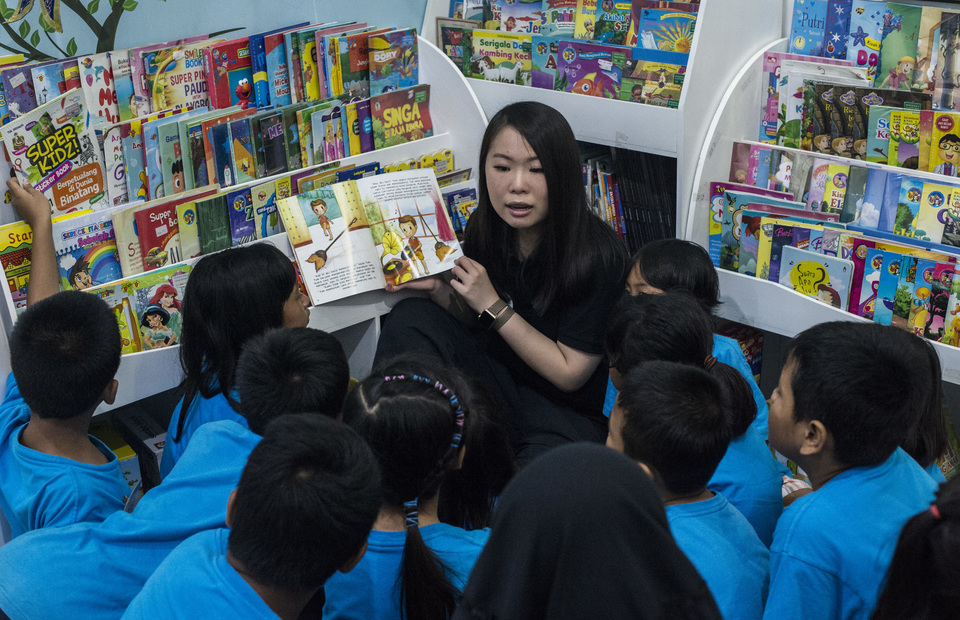 Sabrina Bensawan is seen reading a story book to her students in Saab Shares Study House at Cengkareng, in West Jakarta on Friday (01/02) She founded Saab Shares in 2014 when she was 16 years old. (JG Photo/Yudha Baskoro)
