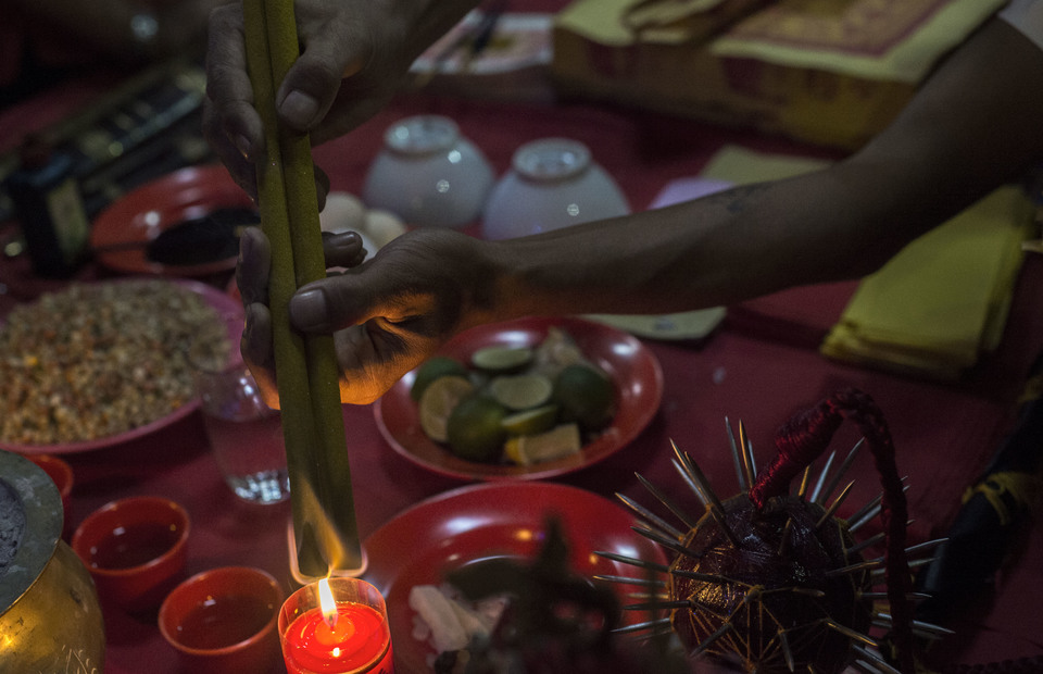 A tatung lights up a incense above table of offerings during Cap Go Meh celebrations on February 18, 2019 in Bogor, West Java. The ancient performance art is believed to call upon holy spirit from their ancestral homes in China that may give positive energy to peoples lives. (JG Photo/Yudha Baskoro)
