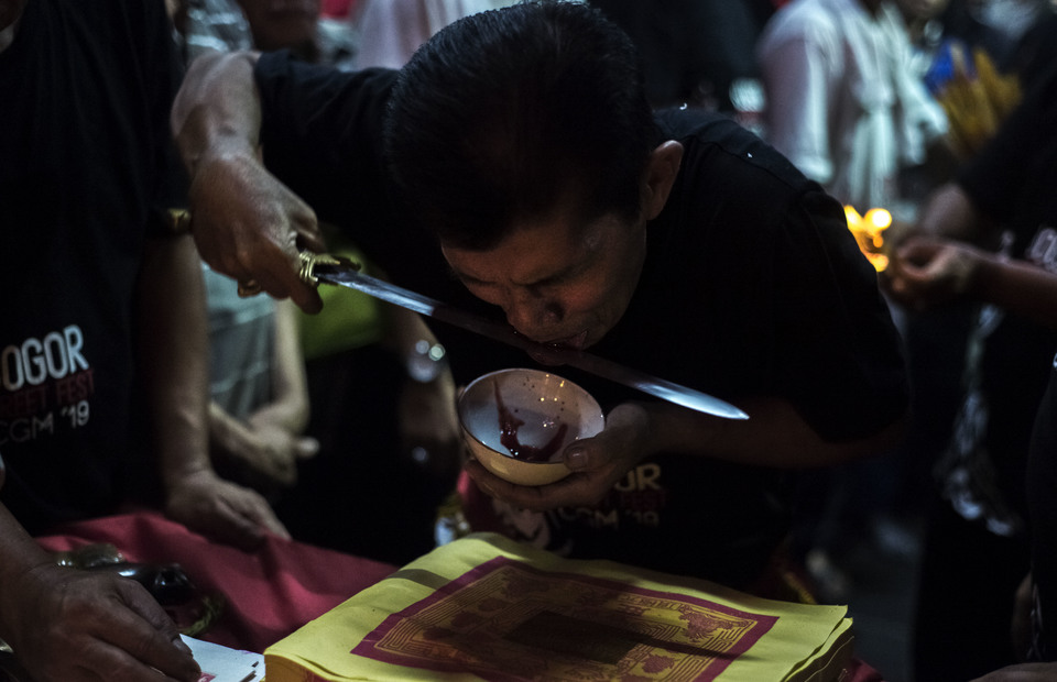 Tatung cuts his tongue during Cap Go Meh celebrations on February 18, 2019 in Bogor, West Java. Tatungs who pray in Dhanangun temple in Bogor, West Java have to cut their tongue as a sin redeemtion and banish misfortune. (JG Photo/Yudha Baskoro)