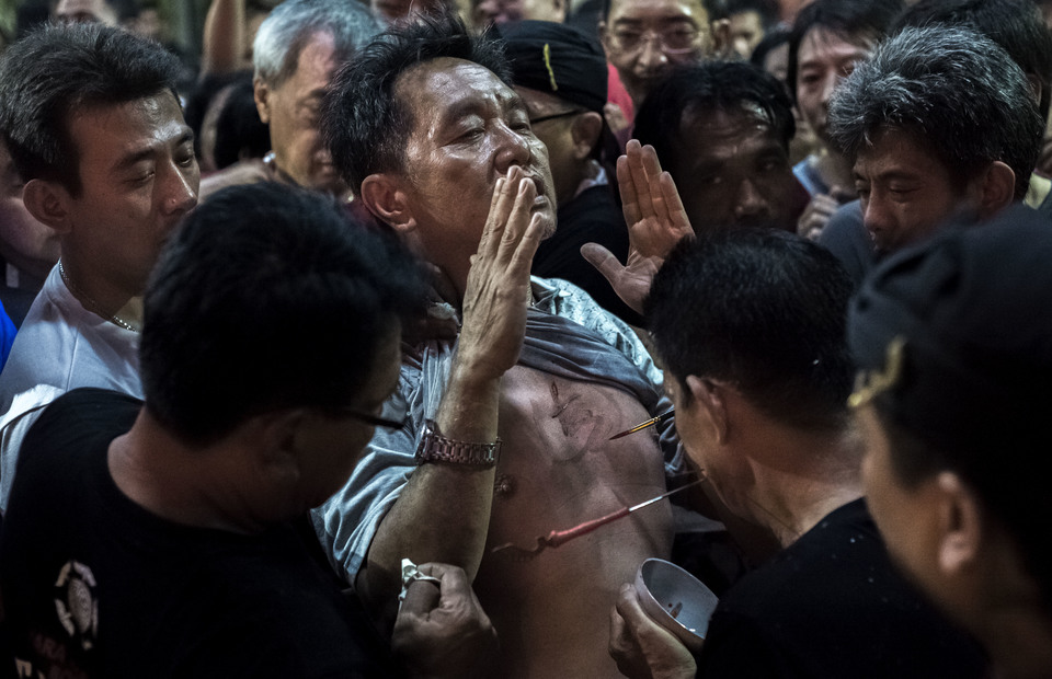 A tatung writes in a mans chest using the tatungs blood during Cap Go Meh celebrations on February 18, 2019 in Bogor, West Java. The man is believed that tatungs blood will gives him a good luck in the year of the pig. (JG Photo/Yudha Baskoro)