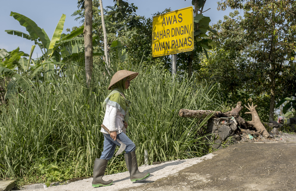 Resident walks in front of Mt. Merapi warning sign in Kalitengah Lor, Sleman regency, Yogyakarta on Sunday (24/02) Following the 2010 eruption,  Indonesian government departments declared a prohibited zone which nobody can permanently stay and no infrastructure is allowed in 9 villages at Cangkringan districts: Palemsari, Pangukrejo, Kaliadem, Jambu, Kopeng, Petung, Kalitengah Lor, Kalitengah Kidul and Srunen. (JG Photo/Yudha Baskoro)