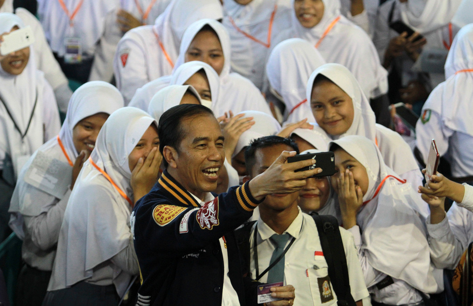 President Joko 'Jokowi' Widodo takes a selfie with school students in Gorontalo on Friday. (Antara Photo/Adiwinata Solihin)