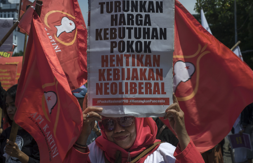 A protester holds up a poster calling on the government to reduce the costs of basic necessities. (JG Photo/Yudha Baskoro)